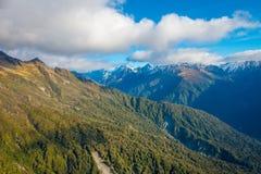 Schöne Landschaft des Neuseelands - Hügel bedeckt durch grünes Gras mit den mächtigen Bergen hinten bedeckt durch Schnee Lizenzfreie Stockfotos