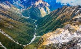 Schöne Landschaft des Neuseelands - Hügel bedeckt durch grünes Gras mit den mächtigen Bergen hinten bedeckt durch Schnee Stockfotos