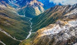 Schöne Landschaft des Neuseelands - Hügel bedeckt durch grünes Gras mit den mächtigen Bergen hinten bedeckt durch Schnee Lizenzfreies Stockbild