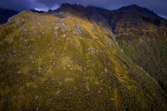 Schöne Landschaft des Neuseelands - Hügel bedeckt durch Gras mit den mächtigen Bergen hinten bedeckt durch Schnee, Süden Lizenzfreies Stockbild