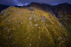 Schöne Landschaft des Neuseelands - Hügel bedeckt durch Gras mit den mächtigen Bergen hinten bedeckt durch Schnee, Süden Lizenzfreie Stockfotos