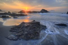 Schöne Landschaft des Sonnenaufgangs durch die felsige Küste Stockfotografie