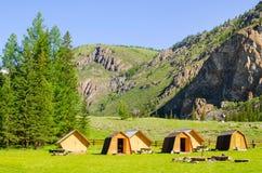 Schöne Landschaft des Tales in Altai-Bergen, kleine Häuser für Touristen, majestätische malerische Ansicht am sonnigen Tag Lizenzfreie Stockbilder