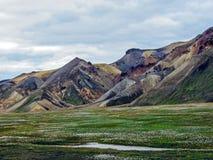 Schöne Landschaft geothermischen Bereichs Landmannalaugar mit Fluss, grüner Rasenfläche und Rhyolithbergen, Island stockfotografie