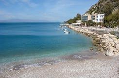 Schöne Landschaft mit azurblauem Meer und einem kieseligen Strand nahe dem Damm des griechischen Erholungsortes lizenzfreie stockfotografie