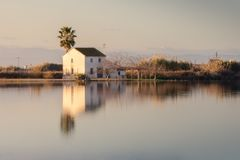 Schöne Landschaft mit Bauernhaus in Albufera-Lagune, in der Reflexion, im blauen Himmel und im gelben Sonnenlicht im Sonnenaufgan stockfotografie