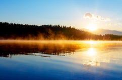 Schöne Landschaft mit Bergen und See an der Dämmerung in den goldenen blauen und orange Tönen Stockbilder