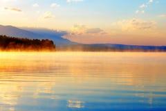 Schöne Landschaft mit Bergen und See an der Dämmerung in den goldenen blauen und orange Tönen Stockfotos