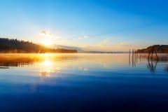 Schöne Landschaft mit Bergen und See an der Dämmerung in den goldenen, blauen und purpurroten Tönen Lizenzfreie Stockfotos