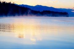 Schöne Landschaft mit Bergen und See an der Dämmerung in den goldenen, blauen und purpurroten Tönen Stockbild