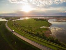 Schöne Landschaft mit einer Fahrt auf der Autobahn die LKWs und einige Autos bei Sonnenuntergang Schattenbild des kauernden Gesch Stockfotos