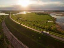 Schöne Landschaft mit einer Fahrt auf der Autobahn die LKWs und einige Autos bei Sonnenuntergang Schattenbild des kauernden Gesch Stockbilder