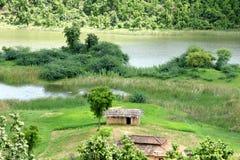 Schöne Landschaft mit Hütten, einem Boot u. Wasser Lizenzfreies Stockfoto