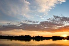 Schöne Landschaft mit Wald und See im Sonnenuntergang Lizenzfreies Stockfoto