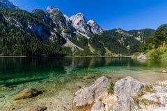 Schöne Landschaft von alpinem See mit haarscharfem grünem Wasser und Bergen im Hintergrund, Gosausee, Österreich Lizenzfreie Stockfotos