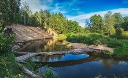 Schöne Landschaft von Waldfluß mit Brücke und Reflexionen von Wolken und von Bäumen Lizenzfreie Stockfotos