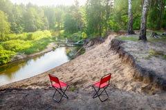 Schöne Landschaft von Waldfluß und von zwei touristischen Stühlen Stockfoto