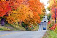 Schöne Landstraße im Herbstlaub Stockfotos