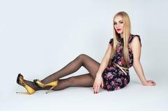 Schöne langbeinige blonde Aufstellung auf einem Hintergrund Lizenzfreies Stockbild