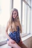 Schöne langhaarige blonde junge Frau, die an sitzt Stockfoto
