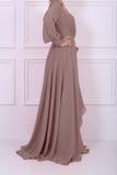 Schöne langhaarige Frau im beige Kleid Stockfotografie