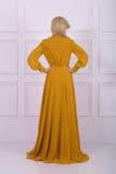 Schöne langhaarige Frau im gelben Kleid Lizenzfreies Stockbild