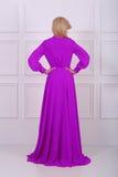 Schöne langhaarige Frau im malvenfarbenen Kleid Stockbild