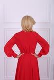 Schöne langhaarige Frau im roten Kleid Stockbild