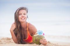 Schöne langhaarige Frau in trinkendem Kokosnusscocktail des Bikinis durch den Strand Lizenzfreie Stockfotos