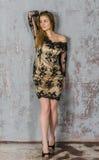 Schöne langhaarige junge Blondine mit einer schlanken Zahl in einem Gold und in einem schwarzen Minikleid Stockfotografie