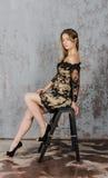 Schöne langhaarige junge Blondine mit einer schlanken Zahl in einem Gold und in einem schwarzen Minikleid Lizenzfreies Stockfoto