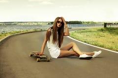 Schöne langhaarige Mädchensonnenbrille sitzt an Stockbild