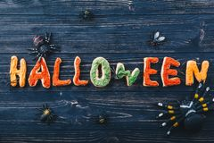 Schöne Lebkuchenbuchstaben für Halloween mit Spinnen und Wanzen auf dem Tisch Süßes sonst gibt's Saures Ansicht von oben Stockfotos