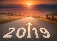 Schöne leere Landstraße bis bevorstehendes 2019 bei Sonnenuntergang
