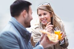 Schöne liebevolle Paare, die Café im im Freien sitzen und Pizza essen stockbild