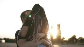 Schöne, liebevolle Paare, die draußen küssen Gut aussehender Mann, der ihre stilvolle Freundin mit Dreadlocks oh seine Arme hält  stock video footage
