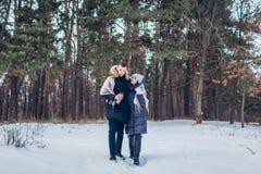 Schöne liebevolle Paare, die zusammen in Winterwald gehen Leute, die Spaß draußen haben stockfotografie