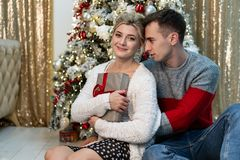 Schöne liebevolle Umarmungen der jungen Leute auf Weihnachtsbaumhintergrund stockfoto
