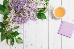 Schöne lila Blumen mit Notizbuch und Tasse Tee Lizenzfreie Stockfotografie