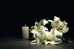 Schöne Lilien und brennende Kerze stockfotografie