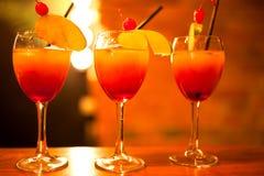 Schöne Linie von drei rot und von gelben farbigen Cocktails lizenzfreie stockfotos
