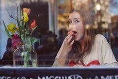Schöne lustige junge Frau, die Nachtisch isst und Kaffee in der Kaffeestube nahe dem Fenster trinkt Stockfoto