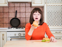 Schöne lustige junge Frau, die Pizza und Burger des französischen Brotes isst Stockfotos