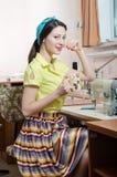 Schöne lustige junge Pinupfrau mit Nähmaschine stockfoto