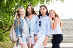 Schöne lustige vier Freundinnen freuen sich und lächeln an der Kamera im Park im Sommer stockbilder