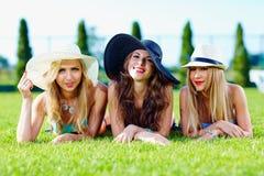 Schöne Mädchen in den Hüten, die auf Sommerwiese sich entspannen Stockfotografie