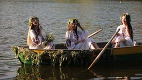 Schöne Mädchen in den slawischen gestickten Hemden in einem Boot, das auf den Fluss schwimmt Mädchen, das in den Kränzen aufwirft stock video