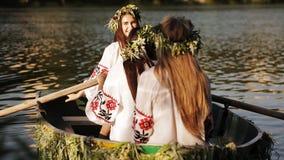 Schöne Mädchen in den slawischen gestickten Hemden in einem Boot, das auf den Fluss schwimmt Mädchen, das in den Kränzen aufwirft stock footage