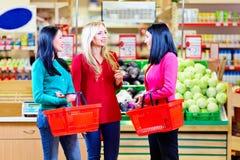 Schöne Mädchen, die im Lebensmittelgeschäftsupermarkt kaufen Stockfotos
