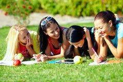 Schöne Mädchen, die Spaß draußen auf grünem Rasen haben stockfotografie